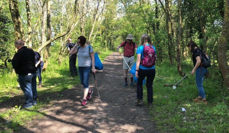 Six people walking along wooded path, picking up litter