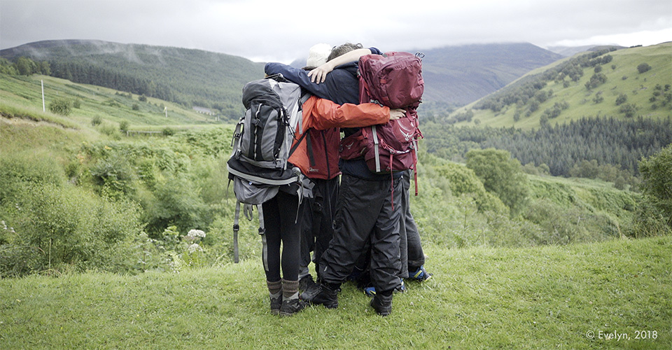 Small group of people, wearing hiking backpacks, hugging on a hill in front of a valley