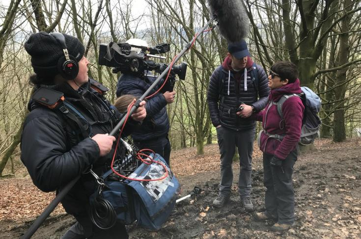 A man and woman standing in a wooded area, being filmed by a film crew of two people