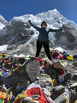 A woman standing in front of a mountains, arms outstretched, surrounded by prayer flags