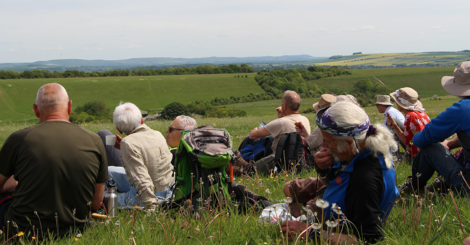 A group of people sitting on a grass slope, enjoying the view