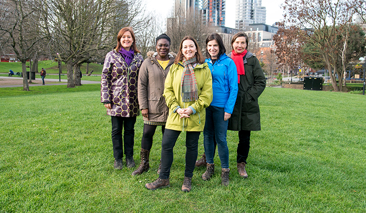 Five women, standing together, outdoors, smiling