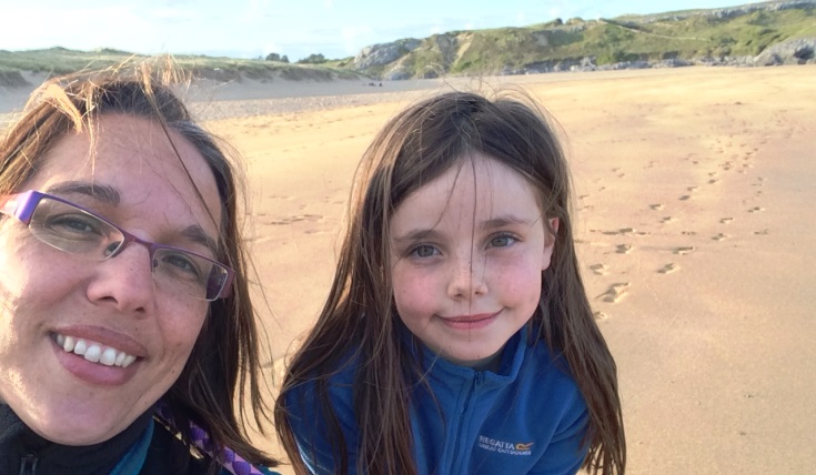Rebecca and her daughter looking at the camera with a beach in the background