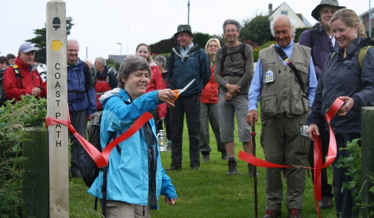 Someone cutting a red ribbon to open a stretch of coast path