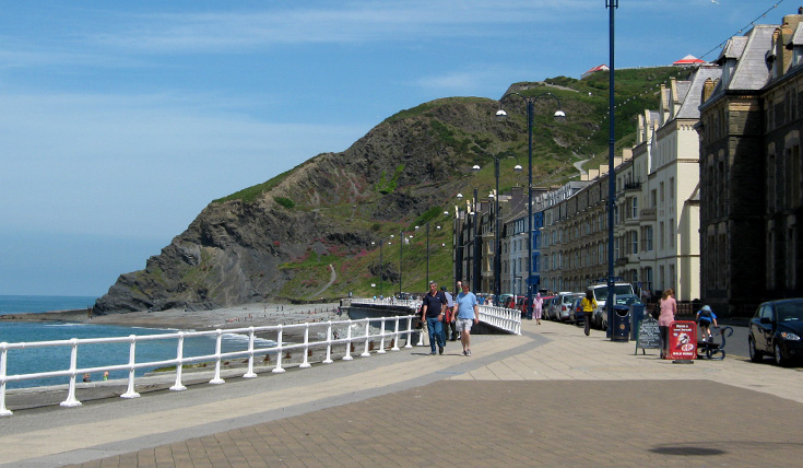 Two people walking along a wide paved prom, beside the sea and a tall cliff