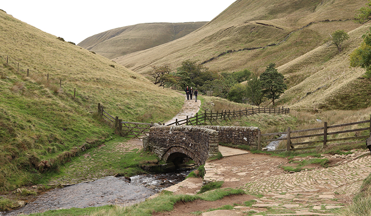 A valley with a stone bridge over a stream and a path running away
