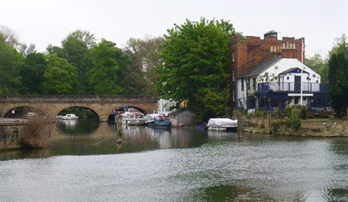 A stone arched bridge beside a large pub