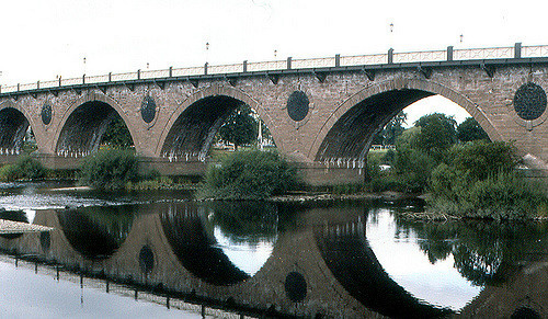 A brick bridge with four arches, over a river