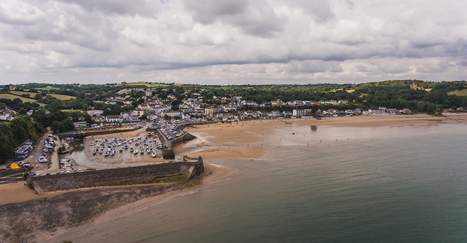 Aerial view of a seaside town with a beach and harbour