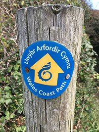 Image of the Wales Coast Path waymarker, on a post