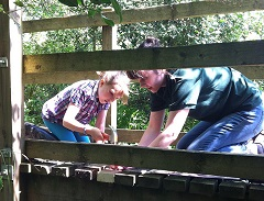 Sarah fixes a bridge with the help of a young volunteer
