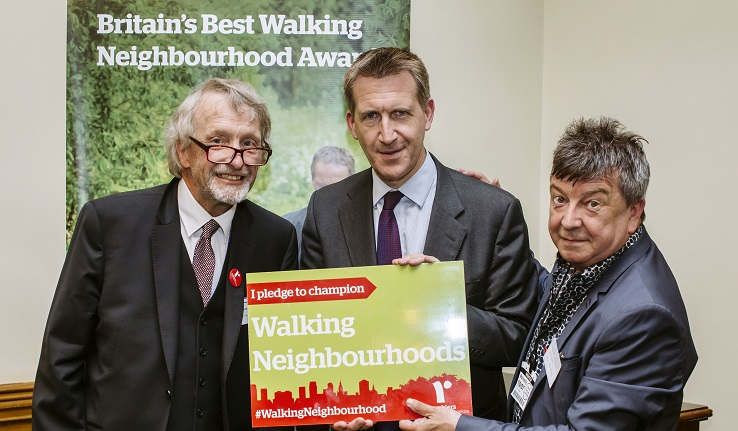 Three men in front of a banner reading Britain's Best Walking Neighbourhood