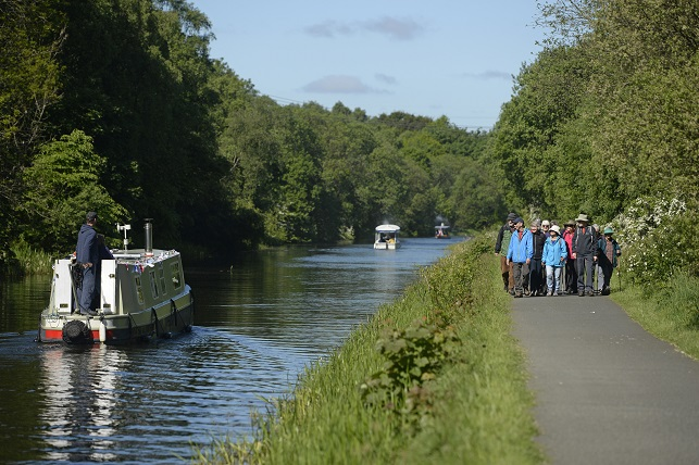 Group of people walking on path next to canal. There is a boat on the canal.