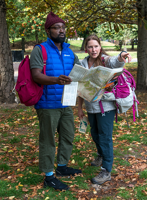 A man and woman, outdoors, wearing hiking clothes and backpacks, looking at a map