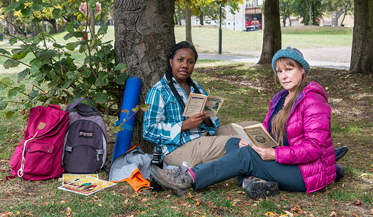 Two women sitting under a tree on grass, reading booklets, surrounded by walking equipment