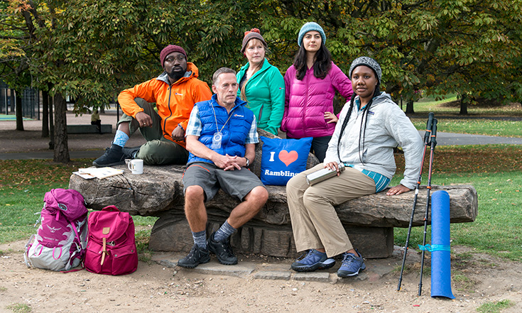 A group of five men and women sitting and standing around a wooden bench, wearing hiking clothing and surrounded by equipment