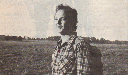 A black and white photo of man standing in a field