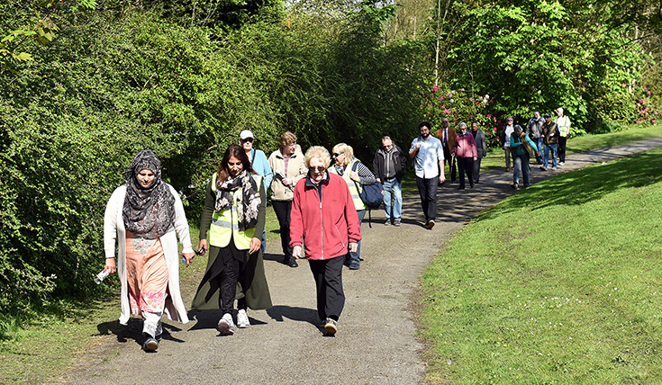A group of older people walking along a park path