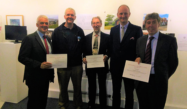 Five men holding up certificates