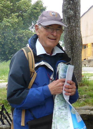An older man outdoors, holding a paper map