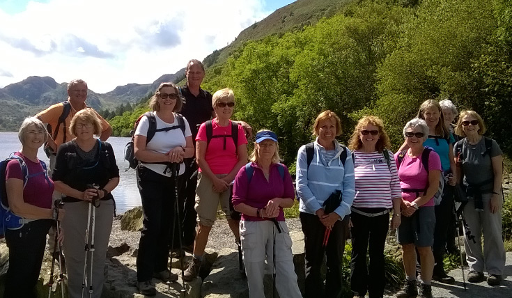 A group of people standing in front of a lake and hills