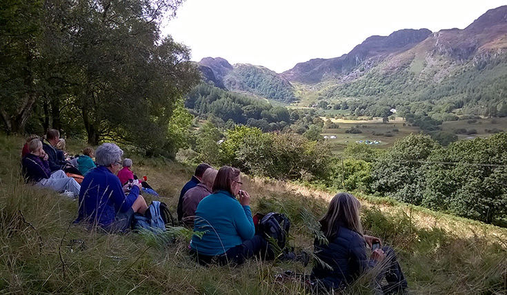 A group of people seated on a grassy hill, looking out at the view in the valley