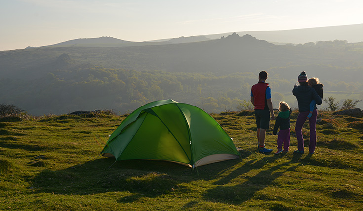 A tent upon a hill, with two adults and two children beside it looking at the view