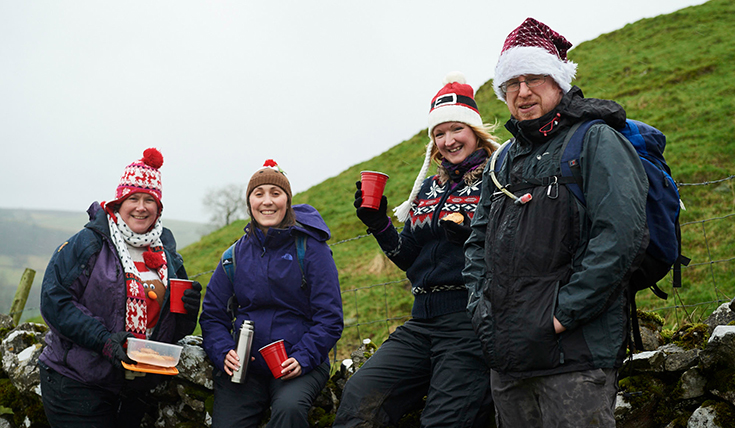 Four people outdoors, wearing Santa hats, drinking from cups