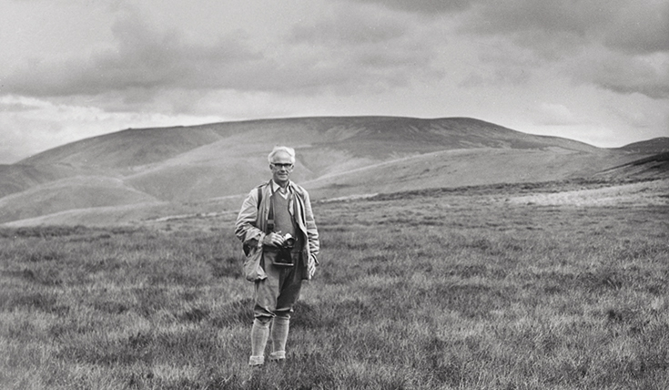 Black and white photo, Man in walking gear in the foreground and hills in the background.