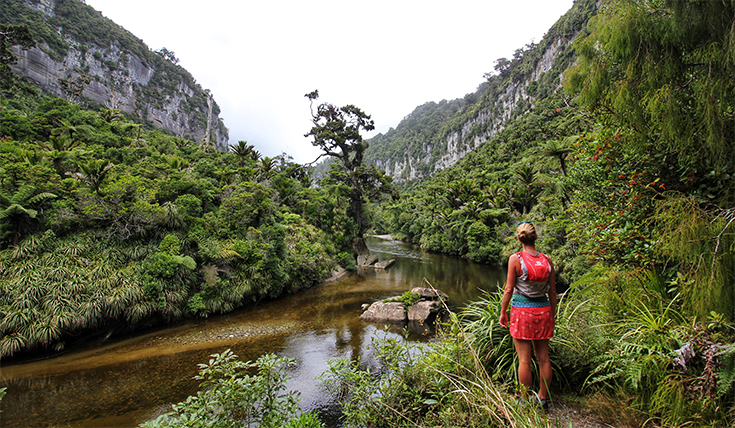 A woman walking a path beside a river in a gorge
