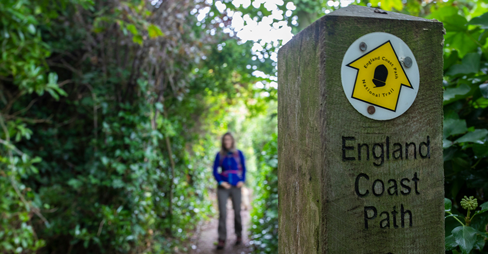 A waymarker reading 'England Coast Path' and a person behind, on a path