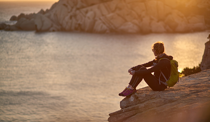 A woman sitting on a rock, beside the sea and a sunset