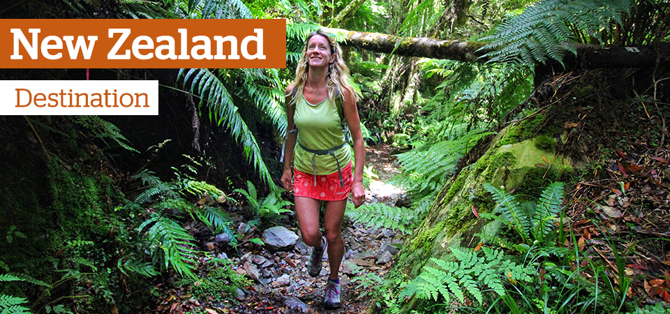 A woman walking a jungle path - Text: New Zealand